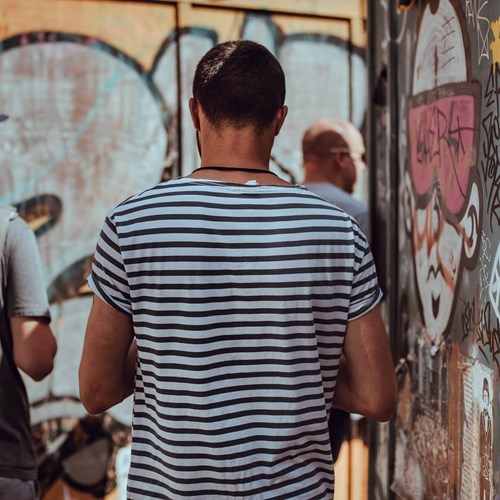 Men exploring streets next to walls with urban art