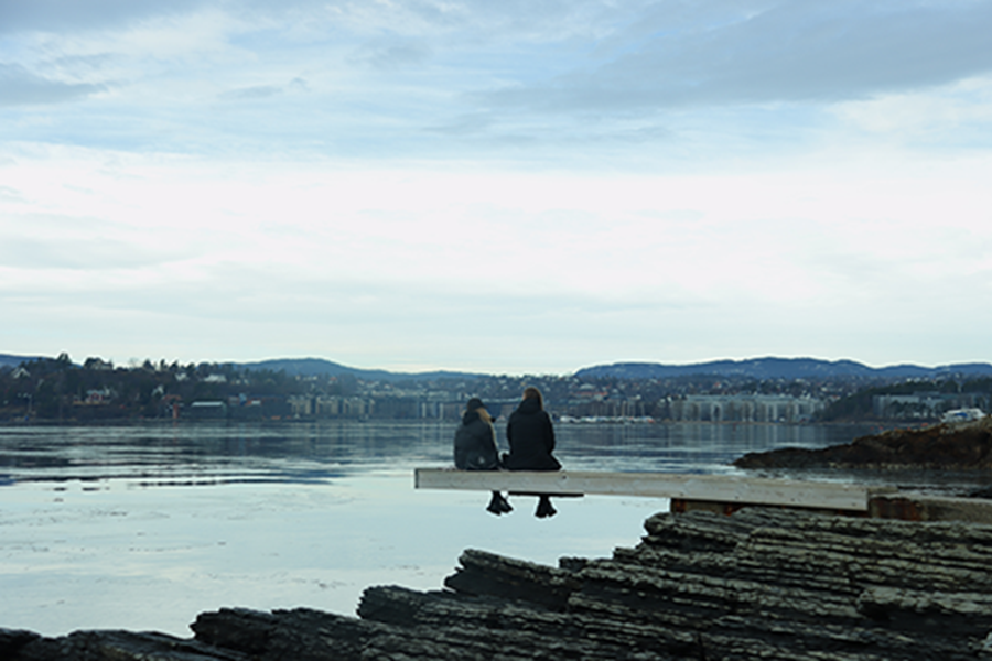 Two Women Sitting on a concrete jetty that overhangs a body of water